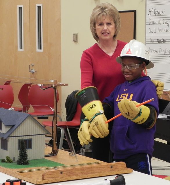 Faye Sill, from Mississippi Power, and PCES student Tyler Swain help spot electrical hazards in Safety City.