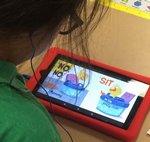 First Grade Student Reading an E-Book