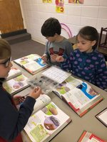 Davis Holloway, Grayson Avant, and Isabelle Saratsiotis identify rocks by their characteristics.
