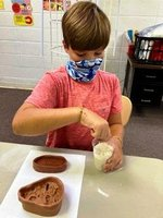 :  Southland Academy fifth grader, Max Kelley, makes a fossil of shells and coral and a fossil of a fish.