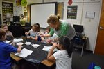 Pictured: Second grade teacher, Lorrie Ledger, guides a group of students as they make lava lamp bottles.