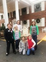 Pictured are Heather Yeiser, Mary Adelaide Yeiser, Mary-Margaret Waddell, Emmie Graft, and Lanier Yeiser deliver the first graders` gingerbread house to the Magnolia Manor for residents to enjoy.  A Magnolia Manor representative is also pictured.