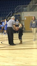Pictured is Southland third grader, Isabelle Saratsiotis, handing the game ball for the women`s basketball game to the head referee.