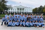 The students are shown in the picture with the White House in the background.