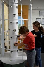 Davis Holloway and Virginia Lanier put their seed pods into the Tower Garden.