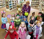 Pictured trick or treating is Mrs. Lori Bell`s class in the library receiving treats from Mrs. Shirley Minchew.