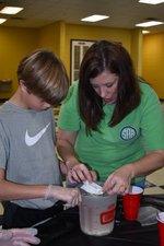 Pictured: Science teacher, Angie Bell, and 5th grader, Bryant Roland, separate curds and whey as they make plastic from milk.