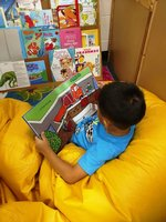 Willy enjoys reading a book in the Reading Center in Mrs. Clayton`s K4 classroom.