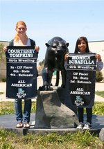 Courtney Tompkins and Monica Bobadilla show their All-American banners that will be on display in the PVHS gym.