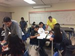 Teacher Manuel Casillas, in yellow shirt, helps students in his summer science class.