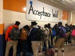 "Students signing the ""I Applied to College Wall"" and listing the schools they applied."