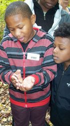 Students having fun holding a worm during a field trip!