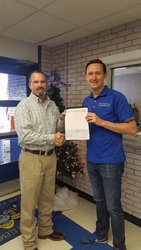 Rodney Blake of McGraw Oil/Kwik Chek presents Principal Brent Fitzgerald the ExxonMobil Educational Alliance Grant
