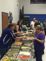 Teachers Stacy Woolsey, Sheila Ferguson, parent Kami Williams, and Board Member Ola Owens help serve the delicious food provided by El Arbol.
