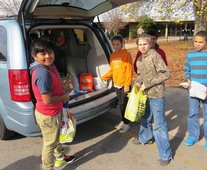 Students help load a van with food collected in the food drive.